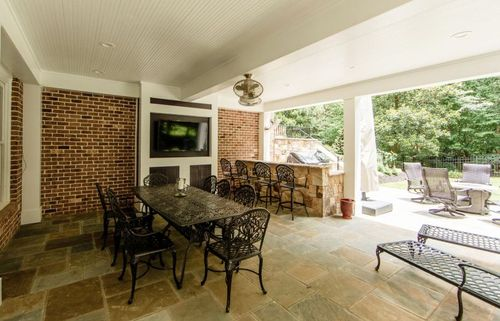 Open air dining area with TV and outdoor kitchen.