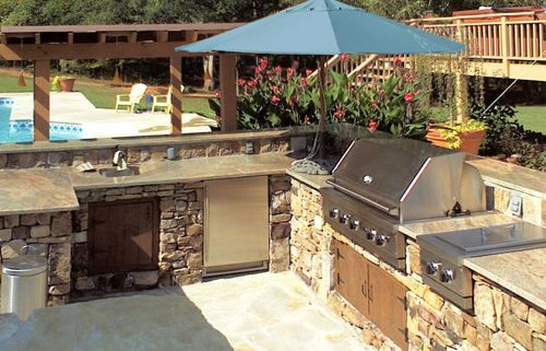 Stone patio leads to an outdoor kitchen.
