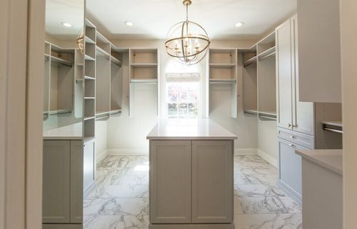 Walk-in closet with shaker cabinets and marble pattern floors.