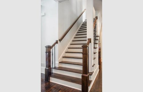 Renovated staircase with contrasting dark steps.