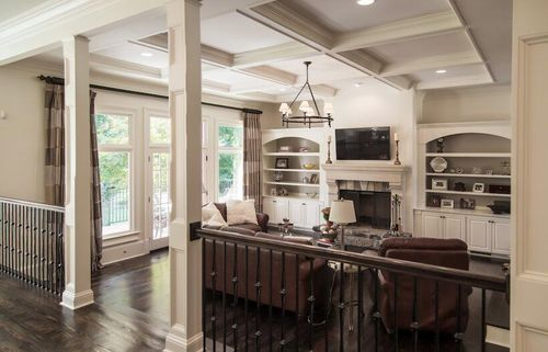 Open concept living room with custom built-ins and decorative pillars.