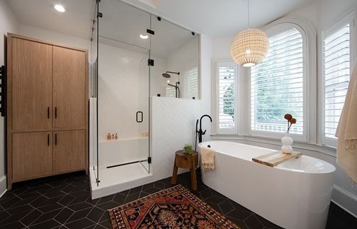 Glass shower with black hardware, accented with bohemian touches in the woven chandelier and medium-stain storage cabinet.