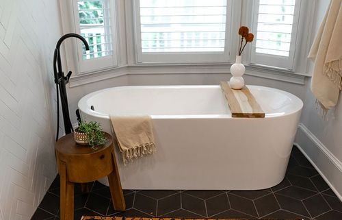 Herringbone patterned wall tile and freestanding tub in front of a bay window. Black hardware make for a sleek and modern finish.