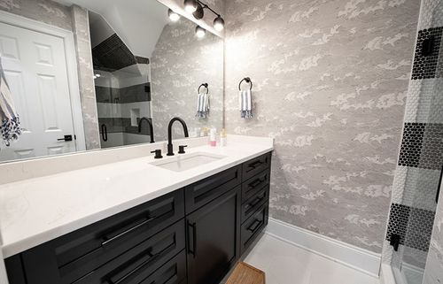 This black and white monochromatic bathroom features illustrative wallpaper and penny round tile that puts an emphasis on texture in this cozy bathroom.