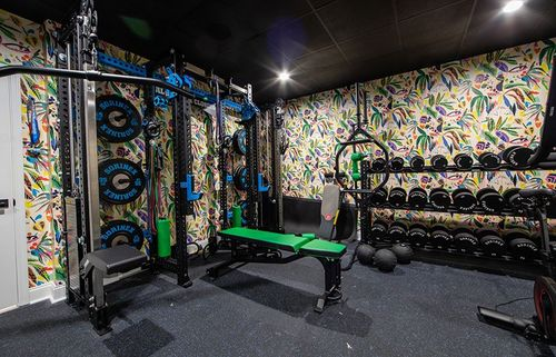 Custom home gym with exciting colorful wallpaper.