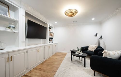 Built-ins with elaborate trim add an elegant touch to this family room. It features plenty of cabinets for added storage and shelf displays up top.