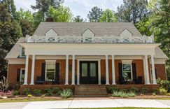 This traditional front porch with a brick facade makes for an inviting entry.