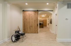 Finished basement with custom arches and an oversized wooden sliding barn door.