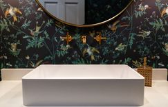Vibrant jungle wallpaper with brass hardware and round mirror.