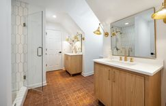 Brass hardware with warm terracotta flooring and medium-stain walnut wood vanities sits surrounded by fresh bright white walls and tile.