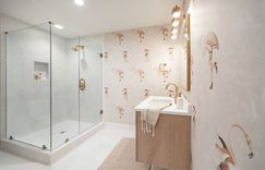 Quirky flamingos sit atop a watercolor blush background and clean white fixtures. Brass accents bring an added warmth to the space.