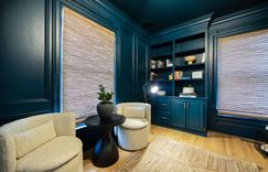 Custom built-in cabinetry painted a monochromatic dark blue-green to match the rest of the room.