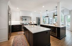 The brass hardware shines in this black and white kitchen. Double islands ensure plenty of room for meal prep and in-kitchen dining.