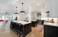 High contrast design scheme with bright white countertops and coal black painted lower cabinets. Double islands face each other underneath modern black pendant lights.